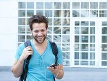 Homem novo de sorriso com telefone celular e trouxa Imagens de Stock Royalty Free
