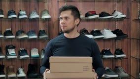Homem novo de sorriso feliz com as sapatas novas da sapatilha em uma sapataria, compra extrema dos esportes vídeos de arquivo