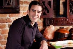 Homem novo de sorriso no café foto de stock royalty free