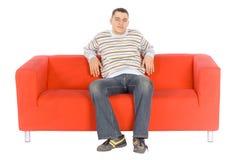 Homem novo de sorriso no sofá alaranjado Fotografia de Stock Royalty Free