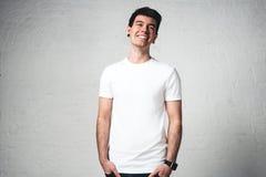 Homem novo de sorriso no t-shirt branco vazio, retrato do estúdio Fotos de Stock