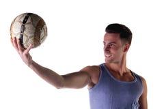 Homem novo de sorriso no tanktop que guarda a bola de futebol Imagem de Stock Royalty Free
