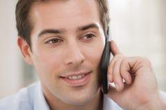 Homem novo de sorriso no telemóvel Imagens de Stock