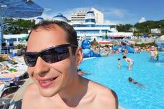 Homem novo de sorriso nos óculos de sol no aquapark Imagens de Stock
