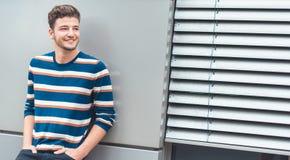 Homem novo de sorriso positivo que inclina-se à parede cinzenta, exterior fotografia de stock