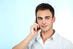 Homem novo de sorriso que aprecia uma conversação com o telefone celular sobre o bl imagens de stock