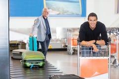 Homem novo de sorriso que espera sua bagagem no aeroporto Foto de Stock Royalty Free