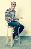 Homem novo de sorriso que fala com suas mãos lisas que sentam-se apenas Fotografia de Stock Royalty Free