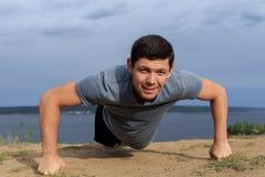 Homem novo de sorriso que faz impulso-UPS fora foto de stock