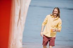 homem novo de sorriso que guarda o vidro com cocktail e que olha afastado ao andar na praia imagem de stock royalty free