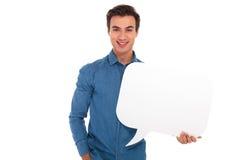 Homem novo de sorriso que guarda uma bolha do discurso Fotografia de Stock