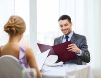 Homem novo de sorriso que olha o menu no restaurante fotos de stock royalty free
