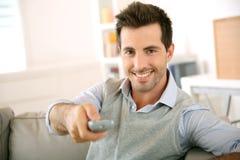 Homem novo de sorriso que olha a tevê Foto de Stock Royalty Free
