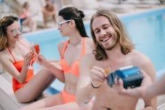 homem novo de sorriso que paga com cartão de crédito ao descansar com amigos fotografia de stock