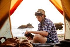Homem novo de sorriso que senta-se perto da barraca e do livro de leitura turísticos Fotografia de Stock