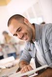 Homem novo de sorriso que tem o livro de leitura do divertimento Foto de Stock