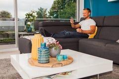 Homem novo de sorriso que texting com seu telefone e que refrigera no sofá fotos de stock royalty free