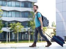 Homem novo de sorriso que viaja com mala de viagem e saco Fotografia de Stock