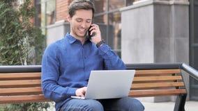 Homem novo de trabalho que fala no telefone, sentando-se no banco video estoque