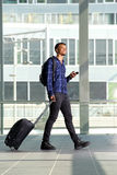 Homem novo de viagem com bagagem e o telefone esperto fotos de stock royalty free