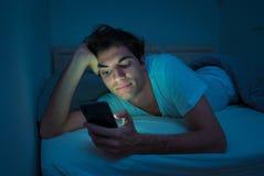 Homem novo dedicado a surfar sem sono dos meios sociais em linha no Internet na cama imagem de stock