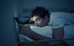 Homem novo dedicado a surfar sem sono dos meios sociais em linha no Internet na cama fotos de stock royalty free
