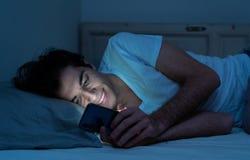 Homem novo dedicado a surfar sem sono dos meios sociais em linha no Internet na cama fotografia de stock