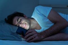 Homem novo dedicado a surfar sem sono dos meios sociais em linha no Internet na cama imagens de stock