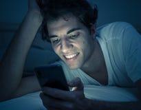 Homem novo dedicado a surfar sem sono dos meios sociais em linha no Internet na cama imagem de stock royalty free