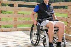 Homem novo deficiente em uma cadeira de rodas foto de stock royalty free