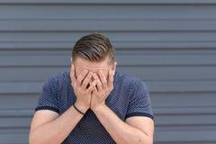 Homem novo deprimido com sua cabeça em suas mãos fotos de stock
