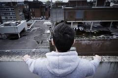 Homem novo deprimido que contempla o suicídio sobre Buildin alto fotografia de stock royalty free