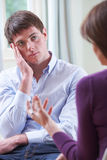 Homem novo deprimido que fala ao conselheiro fotos de stock royalty free