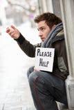 Homem novo desabrigado que implora na rua Fotografia de Stock Royalty Free