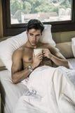 Homem novo descamisado em sua cama com um copo do café ou de chá foto de stock
