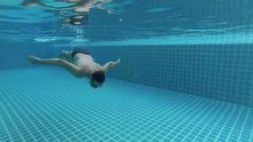 Homem novo desportivo na piscina, vista subaquática Horas de verão das férias Câmera da ação vídeos de arquivo