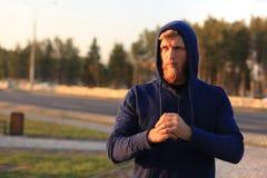Homem novo desportivo seguro com braços cruzados ao estar fora, no por do sol ou no nascer do sol corredor imagens de stock royalty free