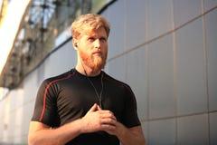 Homem novo desportivo seguro com braços cruzados ao estar fora, no por do sol ou no nascer do sol corredor foto de stock royalty free
