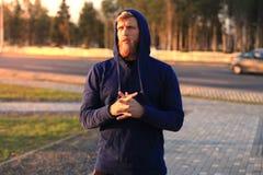 Homem novo desportivo seguro com braços cruzados ao estar fora, no por do sol ou no nascer do sol corredor foto de stock