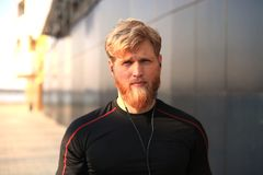 Homem novo desportivo seguro que olha a câmera ao estar exterior, no por do sol ou no nascer do sol corredor fotografia de stock royalty free