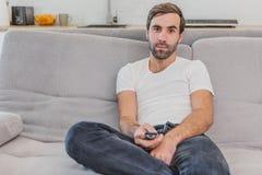 Homem novo divertido bonito que guarda um controlo a distância Durante isto, a tevê está olhando ao sentar-se no sofá em imagem de stock royalty free