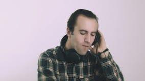 Homem novo DJ que escuta a música em fones de ouvido video estoque