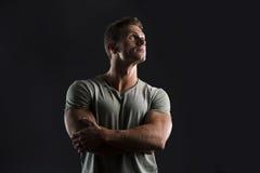 Homem novo do ajuste muscular considerável no fundo escuro que olha acima Imagem de Stock