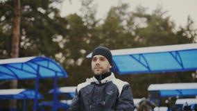 Homem novo do atleta que faz o aquecimento antes do treinamento do exercício no parque do inverno vídeos de arquivo