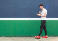 Homem novo do atleta que trabalha no smartphone ao andar no clube de esporte Escritório móvel, autônomo, estilo de vida, mercado  fotografia de stock