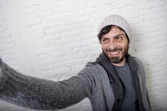 Homem novo do blogger do moderno que guarda fora a imagem ou o vídeo do selfie do tiro do telefone celular da tela fotos de stock royalty free