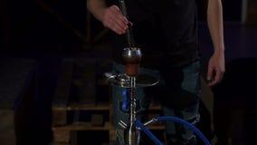Homem novo do cachimbo de água que muda os carvões no cachimbo de água em uma obscuridade Movimento lento video estoque