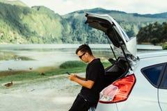 Homem novo do curso nos óculos de sol que sentam-se no tronco de carro que chating no correio do telefone ou da verificação, surf fotos de stock royalty free