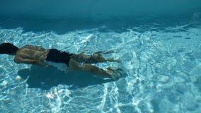Homem novo do esporte com o corpo tonificado que nada debaixo d'água na piscina com água claro temporada de verão na área tropica vídeos de arquivo