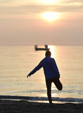 Homem novo do esporte da silhueta que estica o pé após ter corrido o exercício fora na praia no por do sol Imagens de Stock Royalty Free